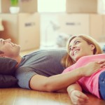 This is a photo of a young couple, a girl with long blond hair and a man with short black hair. The young and cheerful couple just moved in a new apartment. They are lying down on a brown floor, smiling, holding hands, taking a rest and discussing how to decorate their new home.  In the background we can see the room interior in blur.
